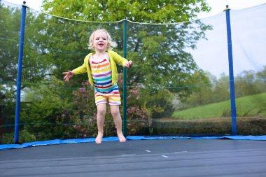 Preschooler girl jumping on trampoline