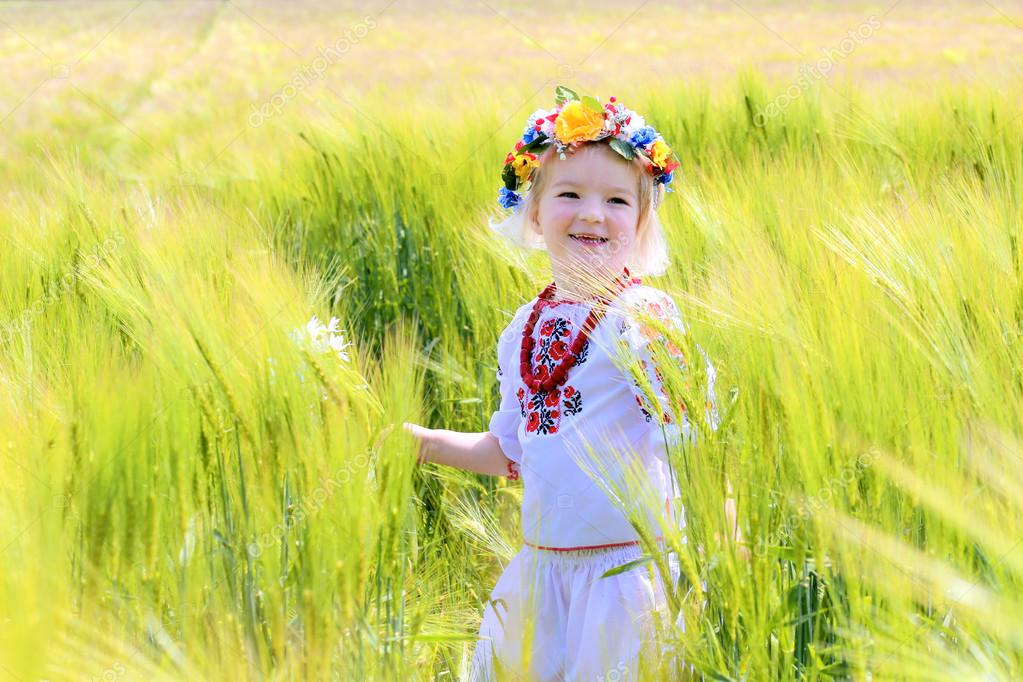 Little girl in Ukrainian dress playing in the field