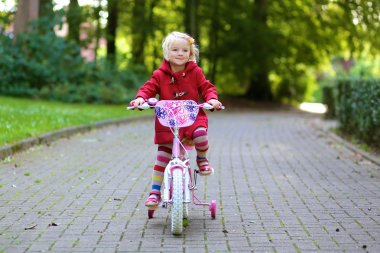 Happy little girl riding her bicycle