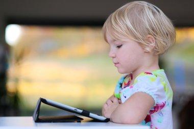 Preschooler girl using tablet pc