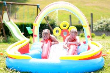 Kids enjoying inflatable swimming pool on summer day