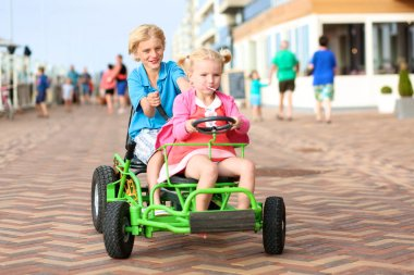 Happy kids riding pedal car on the beach