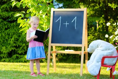 Toddler girl playing teacher with her toys