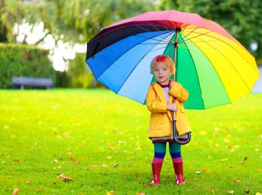 Portrait of playful little girl with colorful umbrella