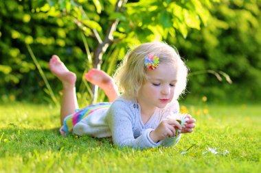 Little kid playing in garden lying in grass