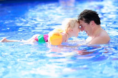 Father and daughter swimming in summer pool