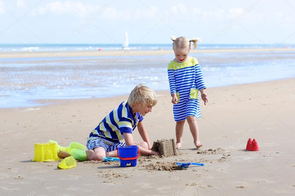 Kids playing with water and sand at summertime
