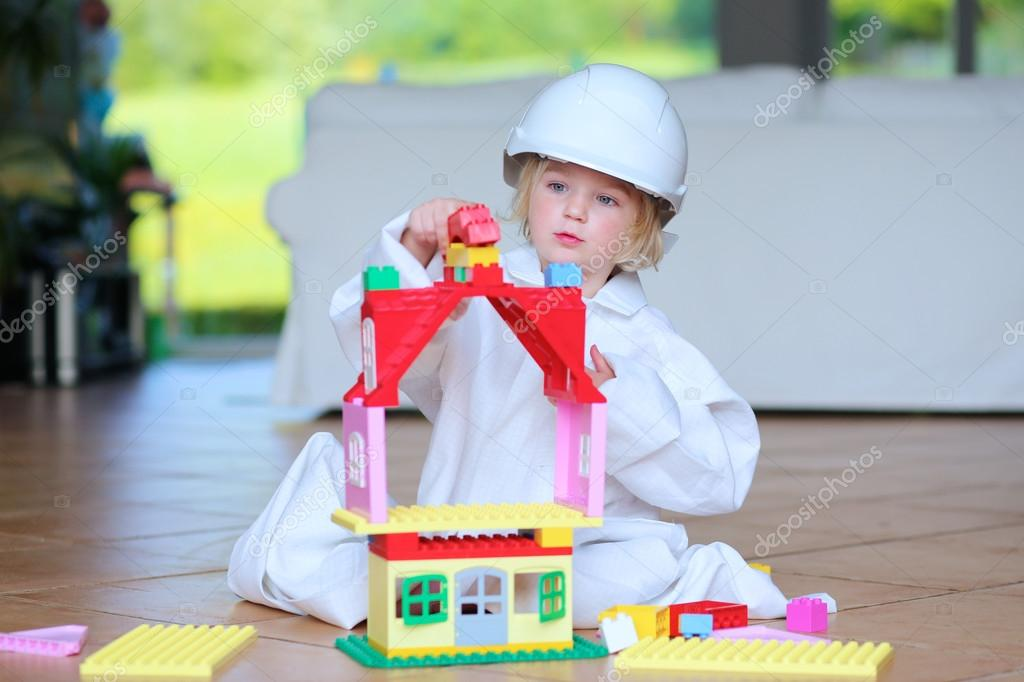 Toddler girl wearing safety helmet playing with building blocks