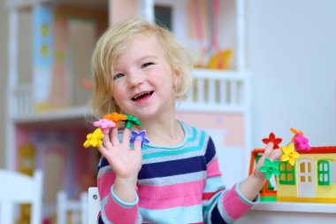 Preschooler girl playing indoors with educational toys
