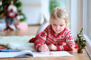 Lovely little girl writing letter to Santa
