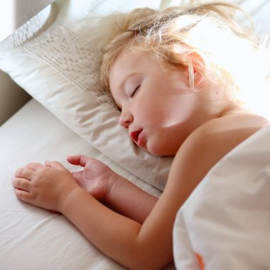 Sweet toddler child sleeping in bed