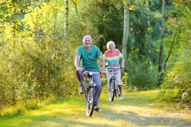 Active seniors couple riding bikes in the forest