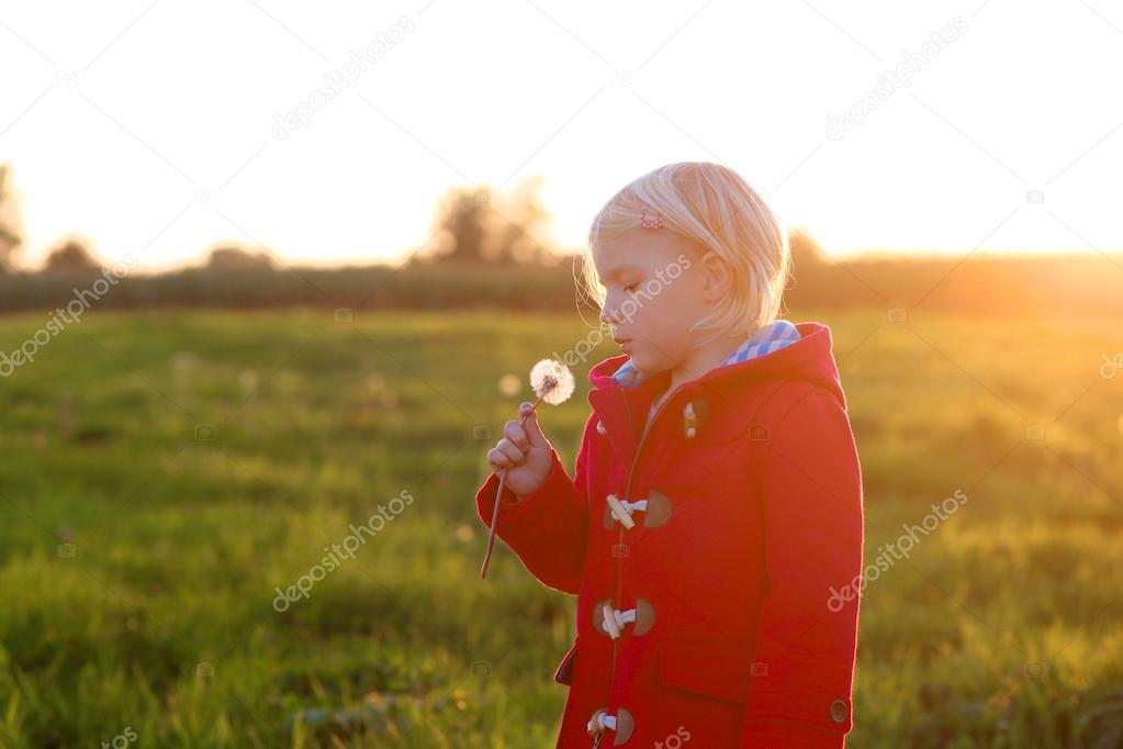 LIttle girl playing in countryside at sunset