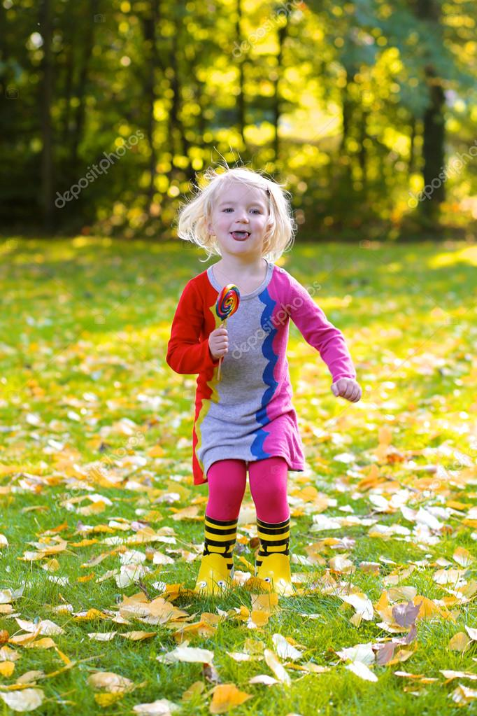 Happy girl with lollipop having fun in autumn park