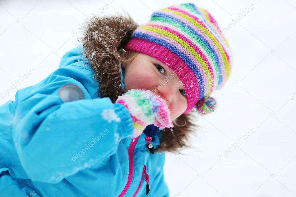 Adorable toddler girl playing in winter forest