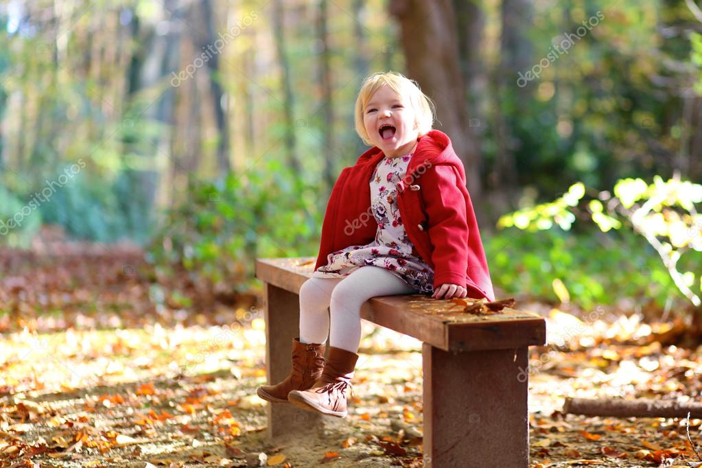 Happy little girl playing in autumn forest