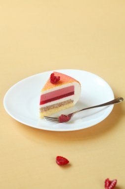 Piece of Layered Vanilla, Raspberry, Peach Mousse Cake, covered with colored velvet spray