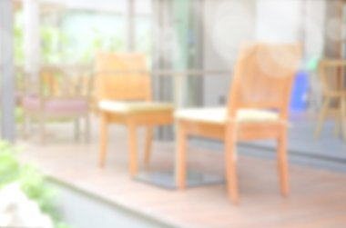 Blurred backyard garden background with dining wood table set.