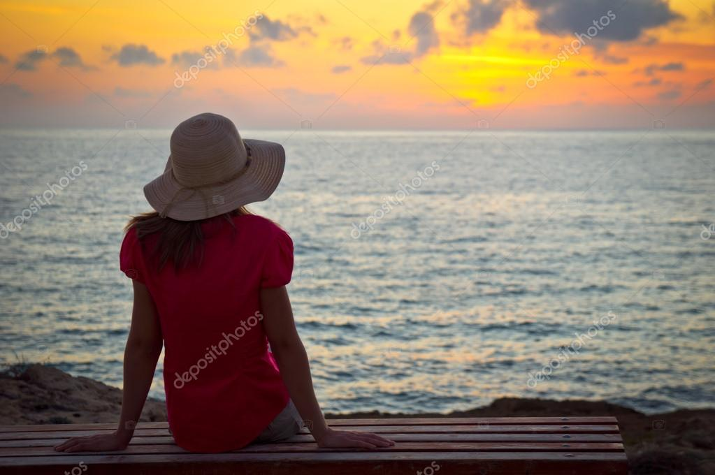 Young woman in hat sitting and looking at sunset