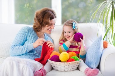 Mother and daughter knitting woolen scarf
