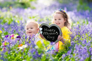 Children playing in bluebell flowers. Little girl and baby boy hold wooden heart shape chalk board. Copy space for your text. Kids having fun outdoors. Birthday or mother's day celebration. stock vector