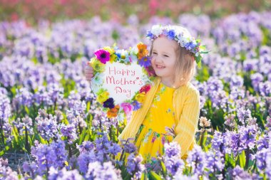 Child playing in bluebells forest. Little girl holding a wooden heart shape chalk board standing in a park with beautiful spring bluebell flowers. Copy space for your text. Kids having fun outdoors in spring. stock vector