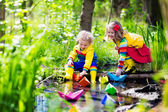 Photo Kids playing with colorful paper boats in a park