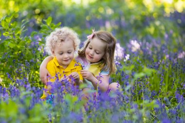 Kids gardening. Children play outdoors in bluebells meadow. Little girl and boy, brother and sister, work in the garden, planting bluebell flowers, watering blue bell flower bed. Family fun in summer. stock vector