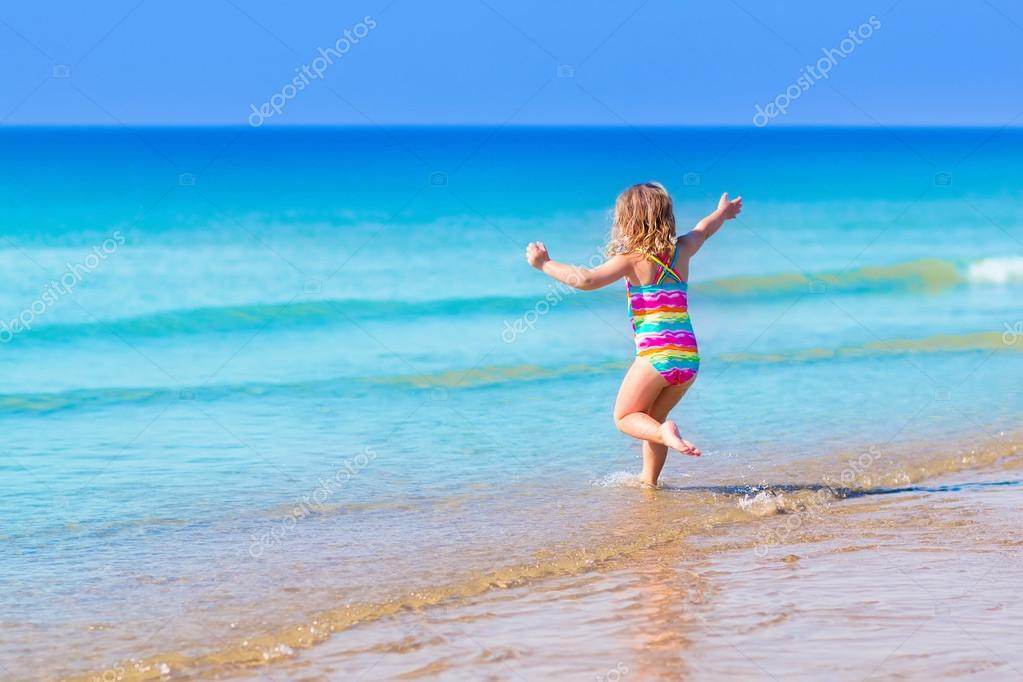 Little girl playing on tropical beach