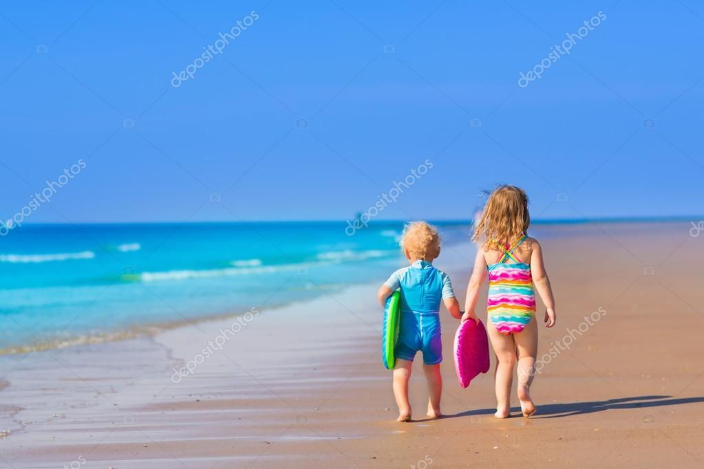 Children with surf boards on tropical beach