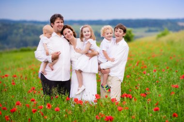 Family with four kids in poppy flower field