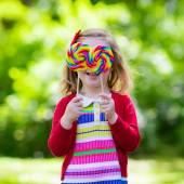 Fotografie Kleines Mädchen mit bunten Süßigkeiten lollipop