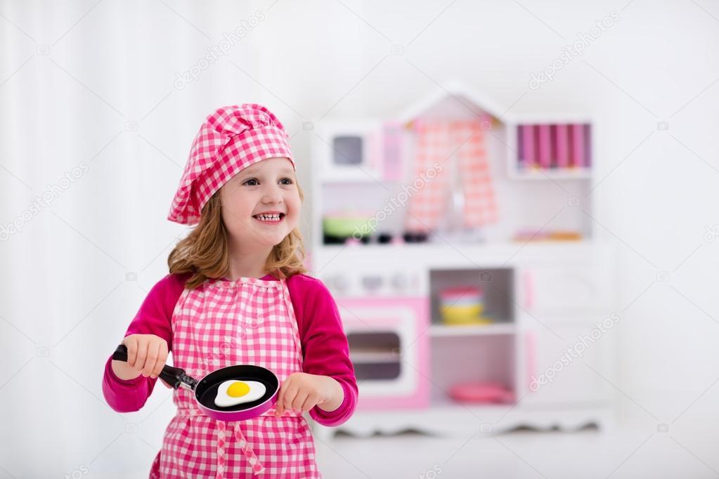petite fille jouant avec cuisine jouet — Photo #114351516