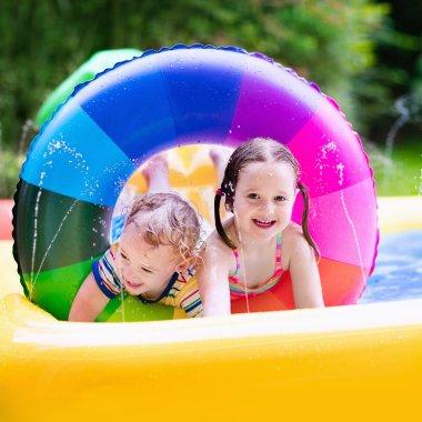Kids playing in garden swimming pool