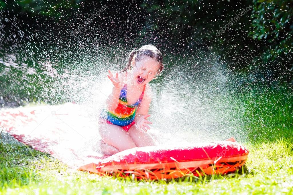Child playing with garden water slide