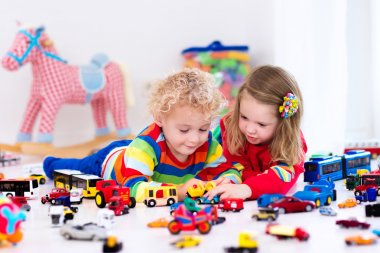 Little kids playing with toy cars