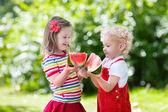 Kinder essen Wassermelonen im Garten