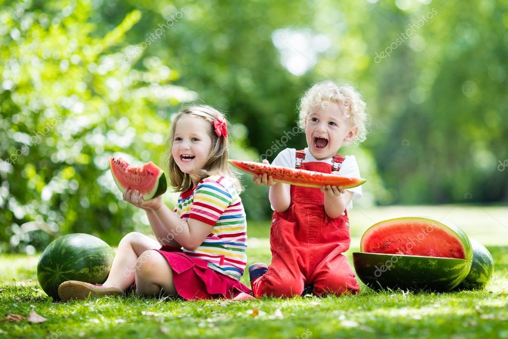 Kinder essen Wassermelonen im Garten — Stockfoto © FamVeldman #117324522