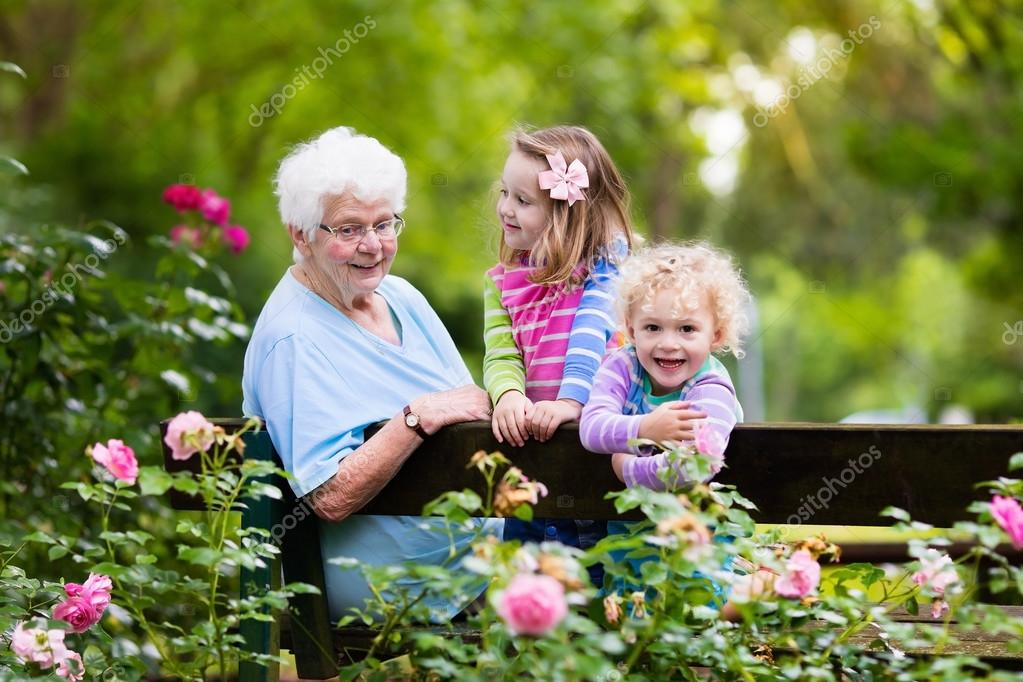 Grandmother and kids sitting in rose garden