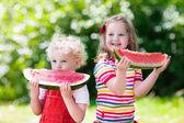 Děti jíst meloun v zahradě
