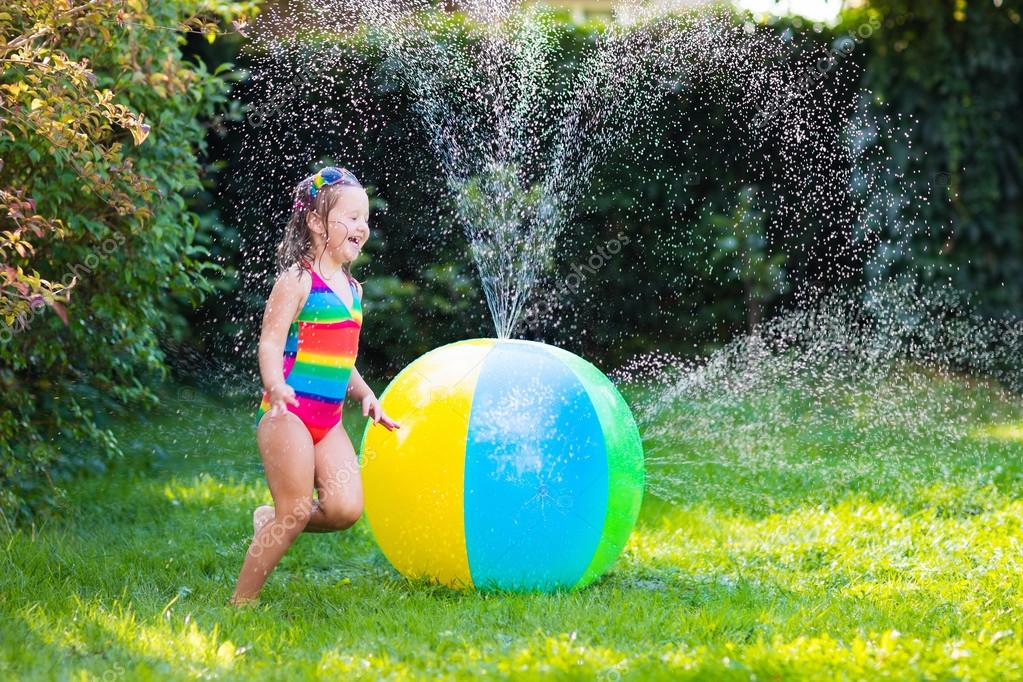Kleine mädchen spielen mit spielzeug ball garten sprinkler