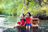 Kinder spielen Piratenabenteuer auf hölzerne Floß