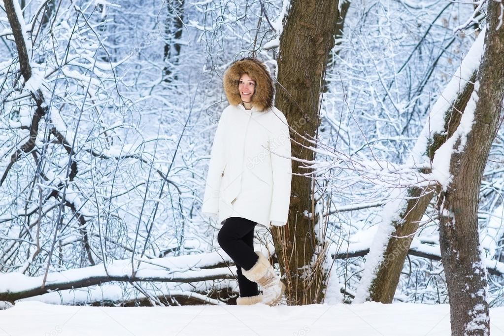 Beautiful young woman walking in a snowy park