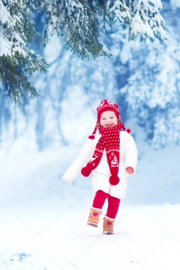 Little girl playing in a winter park