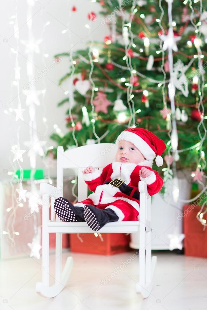 b454866c4c28 Funny newborn baby boy in Santa costume sitting under Christmas tree ...