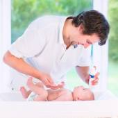 Young loving father changing diaper of his newborn baby son, hol