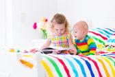 Fényképek két gyerek, egy könyvet, az ágyban olvas