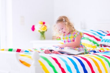 Little girl reading a book in bed