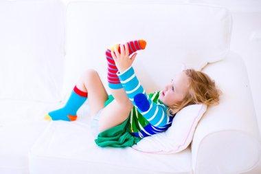 Little girl putting on socks