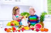 Děti jedí ovoce v bílé kuchyni